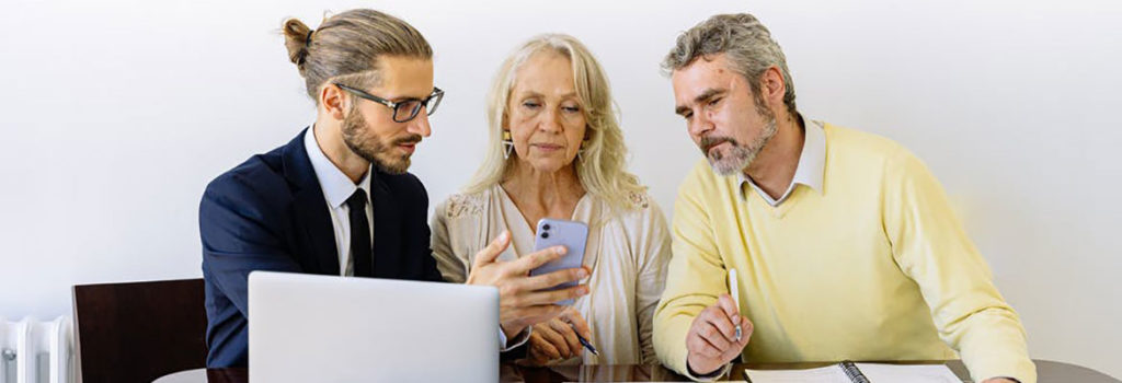 Real estate agent showing clients something on his phone