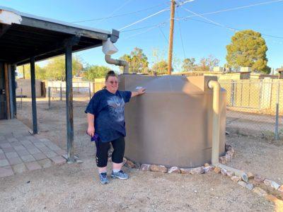 Lora with her rainwater harvesting tank
